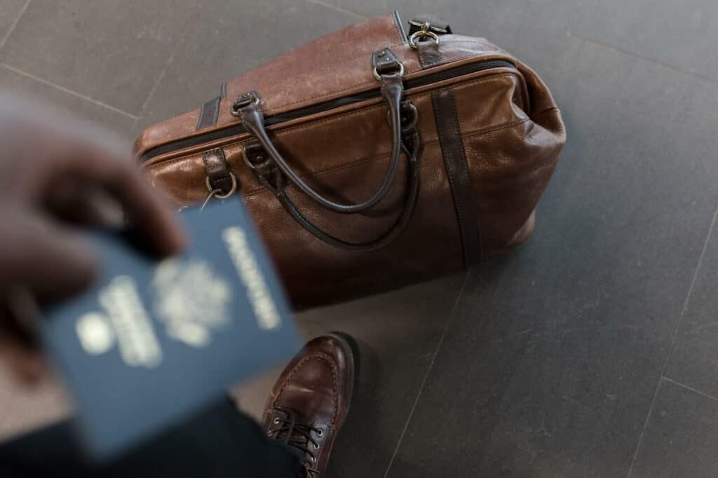 Hand holding travel bags and passports